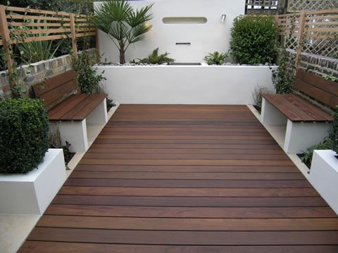 Perfect use of a small space, dark wood decking stands out against the white rendered walls with benches either side, this would look amazing in a back yard or small garden
