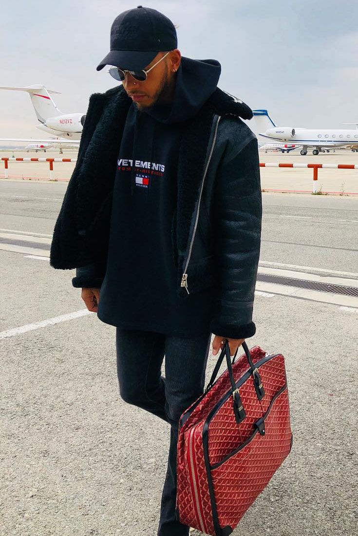 d60a486e Lewis Hamilton jetsets in a Tommy Hilfiger black hoodie and Goyard red  briefcase