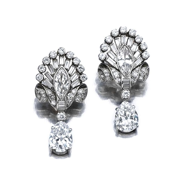 PAIR OF DIAMOND PENDENT EARRINGS,  LATE 1930S. Each surmount of stylised scroll and palmette design, set with circular- and single-cut, marquise-shaped and baguette diamonds, suspending a pear-shaped stone weighing respectively 2.74 and 2.86 carats.