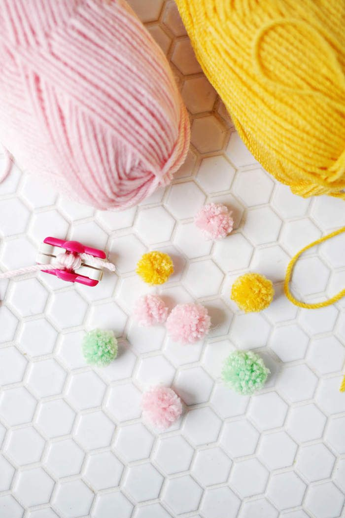 several handmade woolen pompoms, in pale green, pastel pink and bright yellow, gift ideas for mom, pink pompom making tool