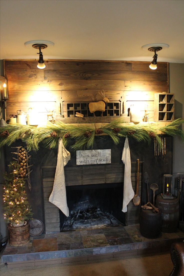 Primitive fireplace. Decorated for Christmas. Stockings, greenery, small tree and reindeer.