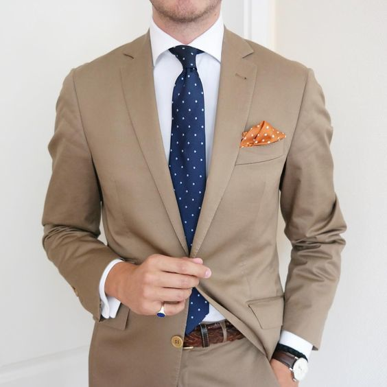 A khaki suit and a white classic shirt will showcase your sartorial self.   Shop this look on Lookastic: https://lookastic.com/men/looks/suit-dress-shirt-tie/20885   — White Dress Shirt  — Navy Polka Dot Tie  — Orange Polka Dot Pocket Square  — Tan Suit  — Brown Woven Leather Belt  — Dark Brown Leather Watch