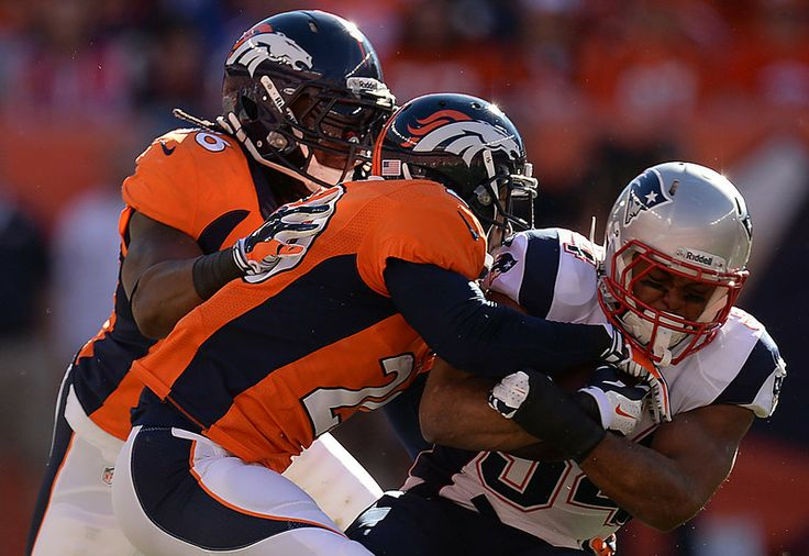 Description of . New England Patriots running back Shane Vereen (34) is tackled by Denver Broncos free safety Mike Adams (20) and Denver Bro...