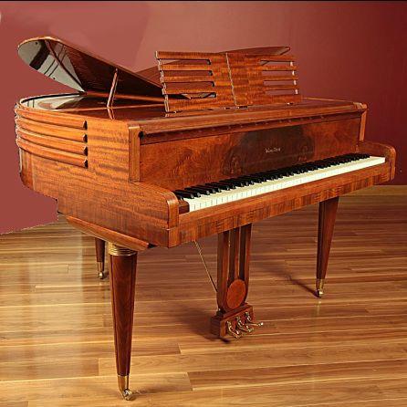 """Um piano de luxo de 88 teclas, estilo Art Deco, Wurlitzer, Modelo 1411, Butterfly. Em meados dos anos trinta, Wurlitzer revelou uma linha de pianos de cauda simétricas, ou grandes """"Butterfly"""". A característica mais notável deste modelo foram as tampas simétricas que se abriam como asas de borboleta. Estas tampas eram cortadas decorativamente para permitir que o som ressoasse através de uma grande abertura F, semelhante a um violino.  Fotografia: Shaupoo."""