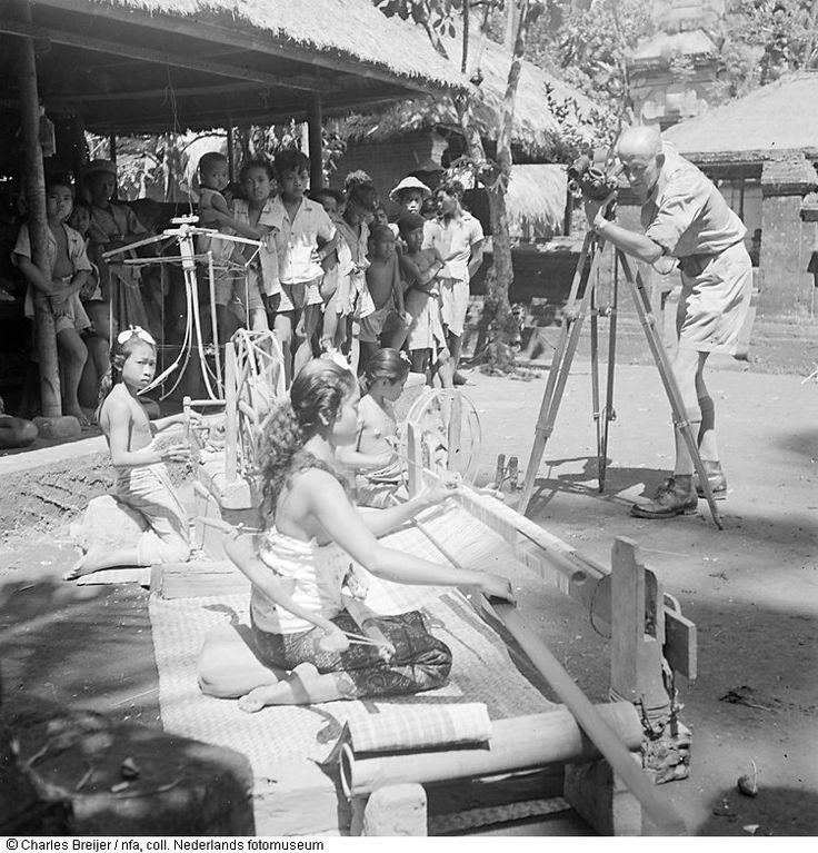 Jaap Zindler filmt in een kampong op Bali twee inheemse meisjes, werkend met een weefgetouw, Indonesië (1947)