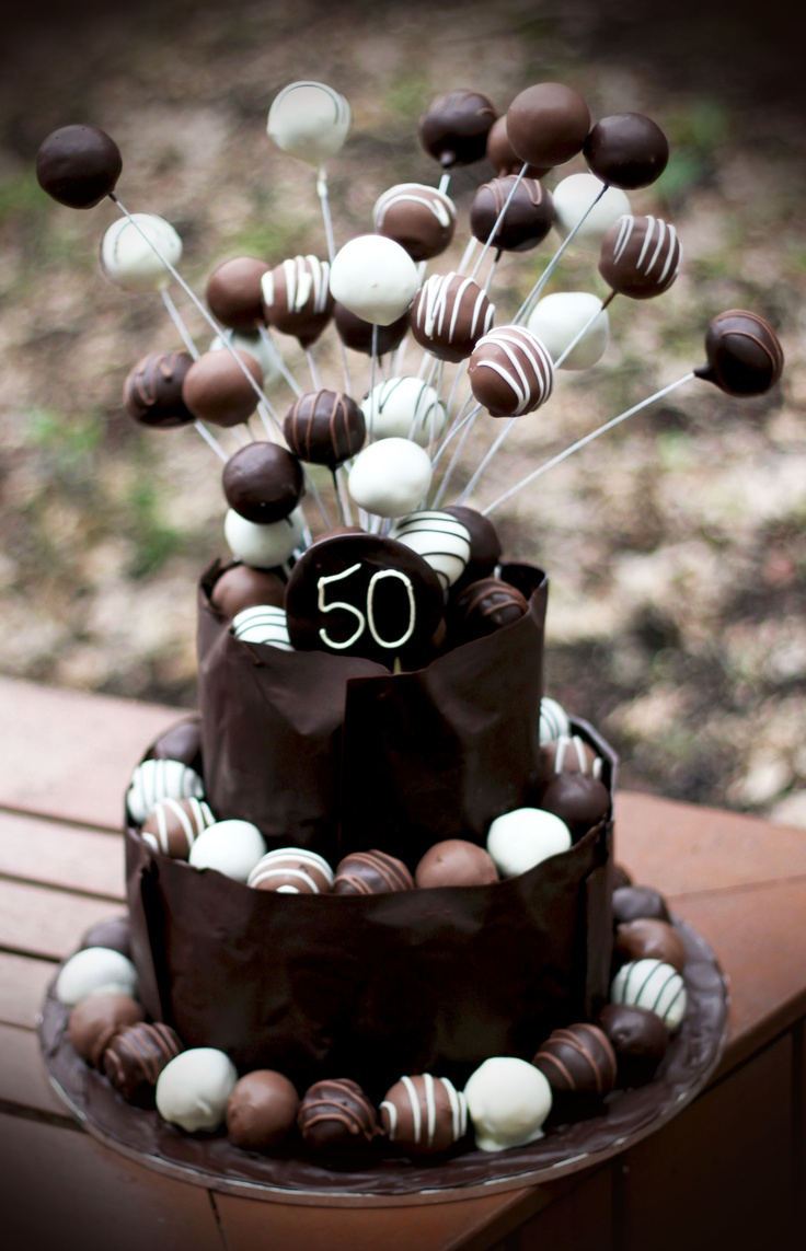 White chocolate mud cake encased in a dark chocolate collar and decorated with a variety of Tim Tam cake pops.