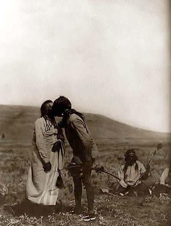 You are viewing an unusual image of an Atsina Indian Crazy Dance. It was taken in 1908 by Edward S. Curtis. The image shows an Indian Kissing another Indian. We have created this collection of images primarily to serve as an easy to access educational tool. Contact curator@old-picture.com.
