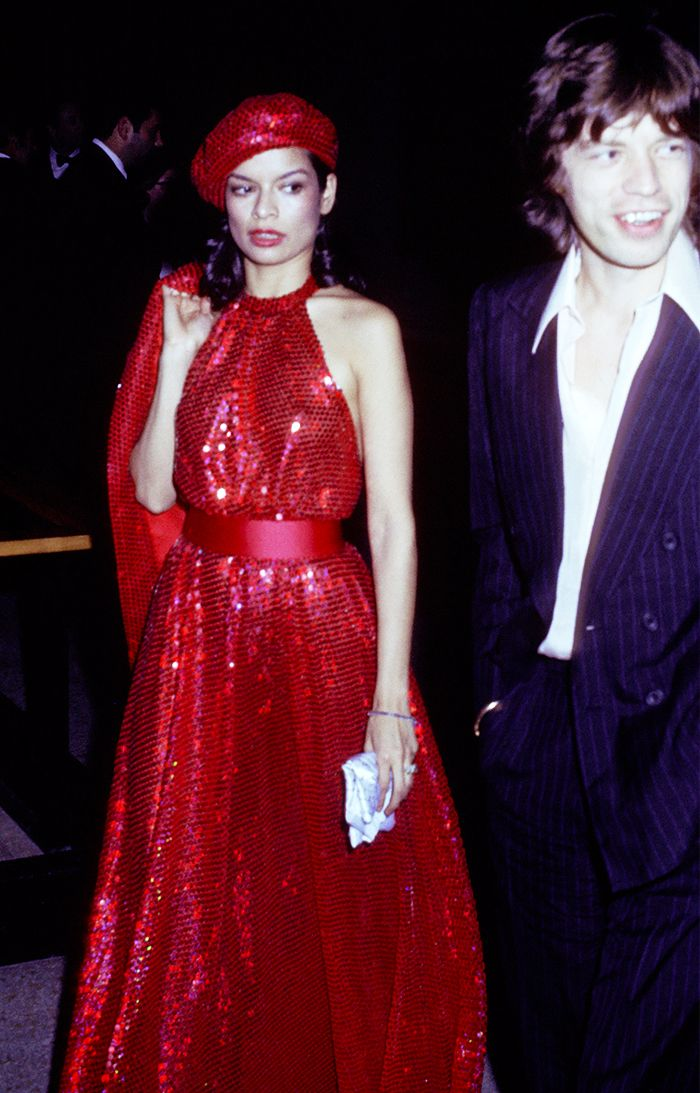 Bianca Jagger in a red sequined dress and matching hat