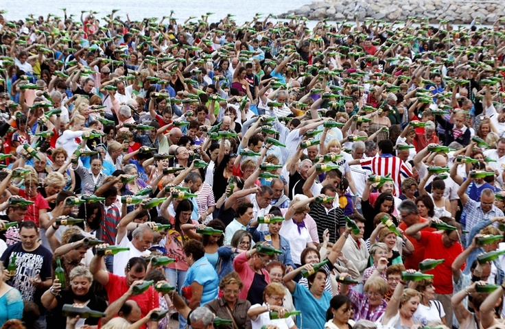 Hundreds of people take part in the world record of cider pouring in Gijon, Asturias, northern Spain, Aug. 24, 2012. About 7,883 people participated and the record was achieved.