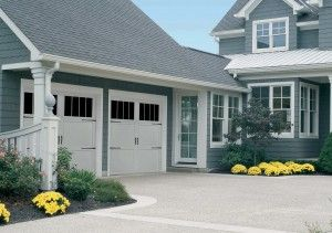 white garage doors with black hinges and window inserts