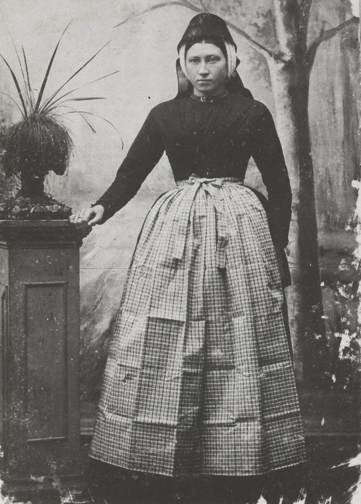 The Netherlands, Terschelling. Vrouw in Terschellinger streekdracht. De vrouw is gekleed in de zondagse dracht van Oost-Terschelling. Ze draagt een effen groen jak en Tibet rok en een bont schort. Op het hoofd draagt ze de 'driestrooksmuts', met daarover de zwarte kap. Om de hals een bloedkoralen snoer met gouden slot. ca 1895 #Terschelling