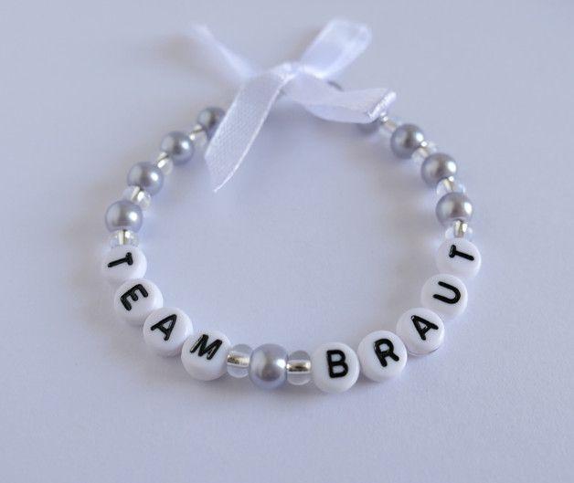 Armband Team Braut   Das Armband ist auf Gummi aufgezogen.  Es besteht aus fliederfarbenen Glaswachsperlen und kleinen Glasperlen mit Silbereinzug. Verziert wird das Armband durch eine weiße...