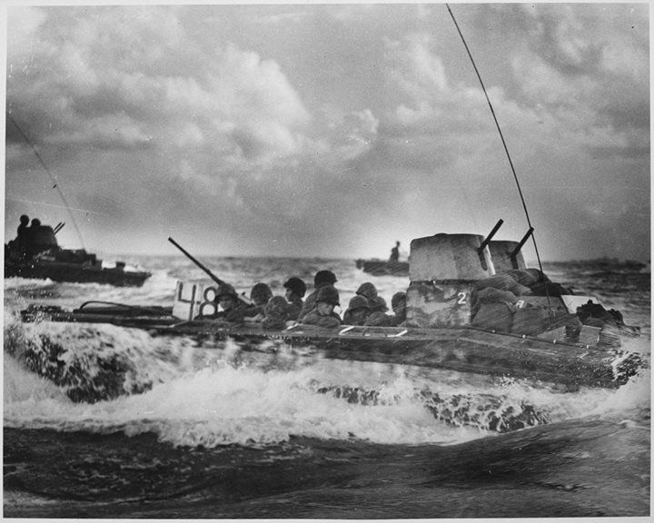 A Water Buffalo loaded with Marines churns through the sea bound for beaches of Tinian Island near Guam 1944.