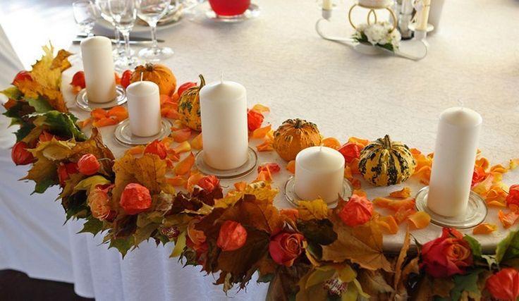 arrangement de table pour l'automne composé de physalis alkekengi, feuilles automnales, mini citrouilles et bougies piliers