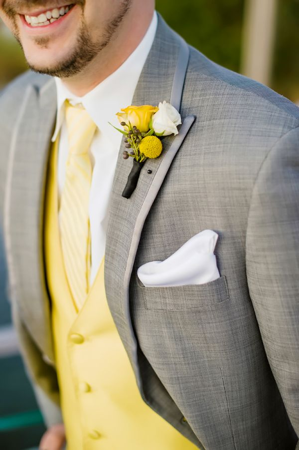 Pair a lemon yellow waistcoat and boutonniere with a soft grey suit for a sophisticated yet modern groom's outfit.