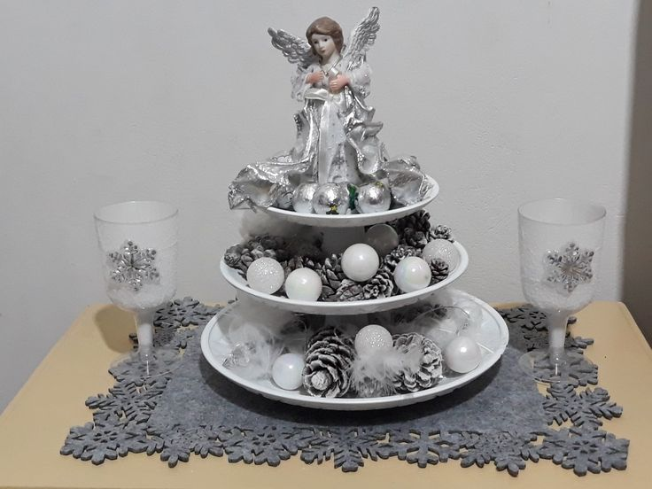 DIY cake stand with pincones, feathers Xmas tree ornaments a beautiful silver angel in the top and some yummy xmas chocolates. On the side it's 2 plastic wine glasses covered with  Epson sold and a snowflake sticker, don't forget to add a battery operated tea light inside.