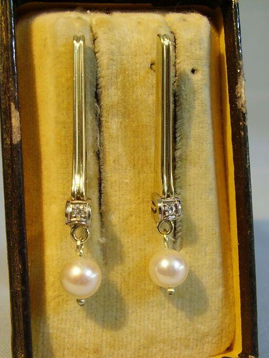 Gold diamond Stud Earrings stud earrings 0.10 ct met echte Akoya parels  De oorbel zijn gemaakt van 585 / 14 kt geel goud en zijn hallmarked dienovereenkomstig op de pennen. De oorbellen hebben groef bars en diamanten ingesteld in wit goud millegrain-instellingen. De diamanten total 0.10 ct één gesneden VVSI onder elk een echte witte Akoya Parel van is fijne glans en glorieuze glans flexibel opgehangen.Zodat de oorbellen beter op het oor zitten werden ongedragen gepatenteerde rug…