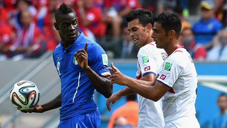 Mario Balotelli of Italy holds the ball and gestures twoard Giancarlo Gonzalez and Michael Umana of Costa Rica