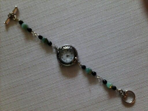 A watch with a silver plated face with a stainless steel back