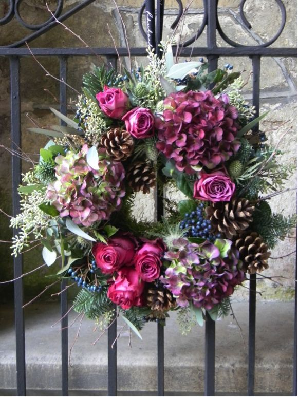 Christmas Wreath - Scented Roses,Hydrangeas & Woodland Foliage Handmade by our expert floral design team in Winslow.This fresh wreath is made to order. Using the freshest of flowers and foliage this will charm any visitors at your door. A wonderful combination of magenta roses , green foliages and fruitful berries along with hydrangeas and pine cones.