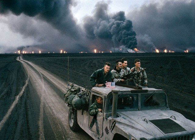 "FIELDS OF FIRE U.S. Marines in Kuwait, with the Burgan oil field burning in the distance, February 1991. From Vanity Fair, October 2013, ""Dave Eggers on the 1990s, the Decade That Began With Hope and Ended Just Before The Fall"""