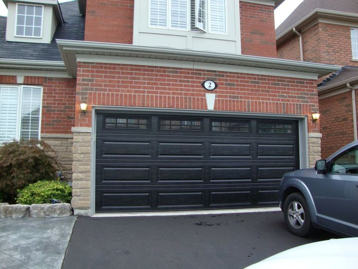 Black garage doors with brick