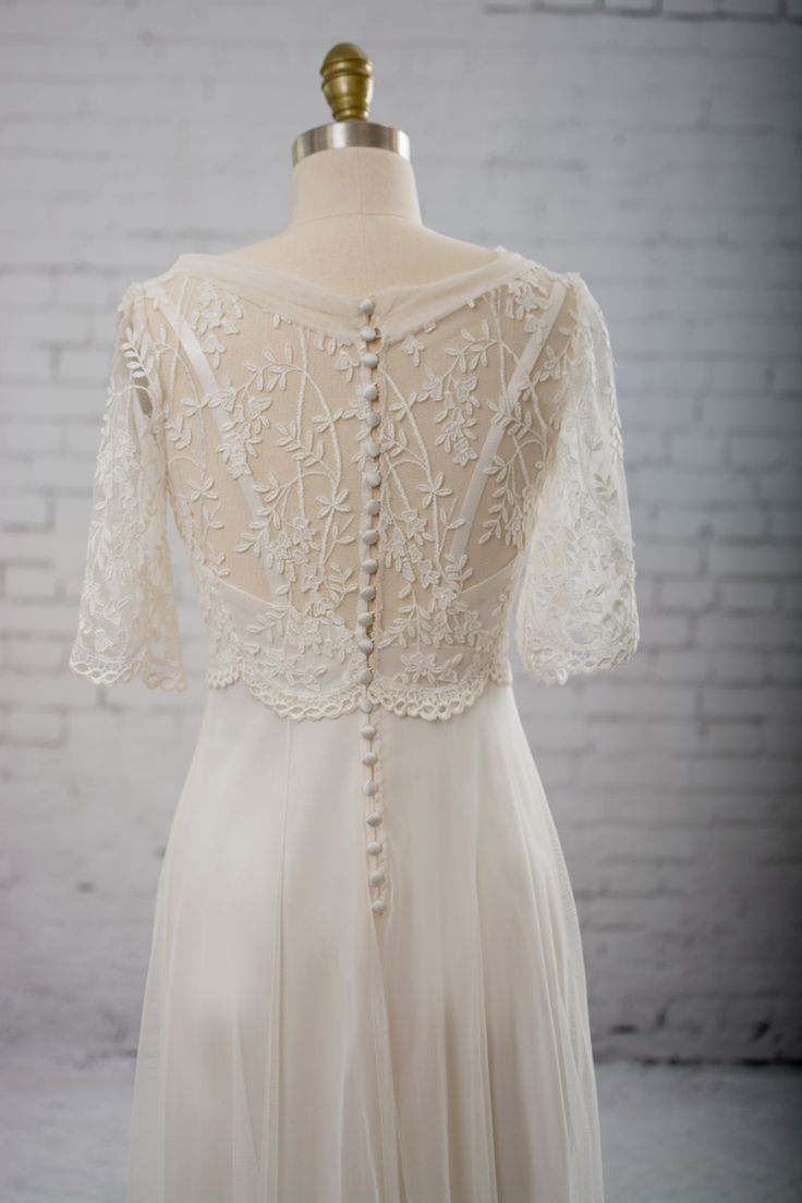 Bodice of scalloped embroidered tulle with a leaf-and-vine motif, bell sleeves, and a v-neck with a collar of cotton netting. Satin button back closure. Empire waist and skirt of cotton netting. The s