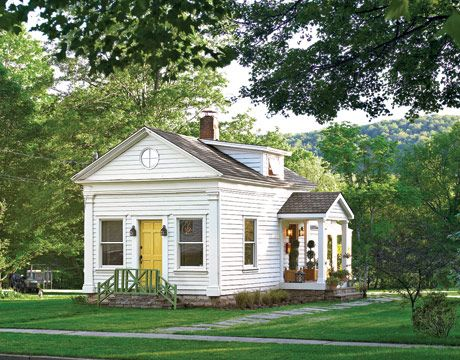 tiny house cottage economical | small white cottage with yellow door surrounded by trees