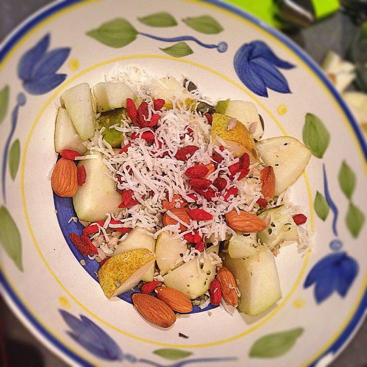 Fresh fruit salad with nuts seeds and coconut and goji berries