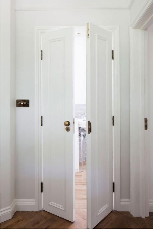 Bi fold bathroom doors adorned with brass door knobs open to a lovely bathroom with wood ...