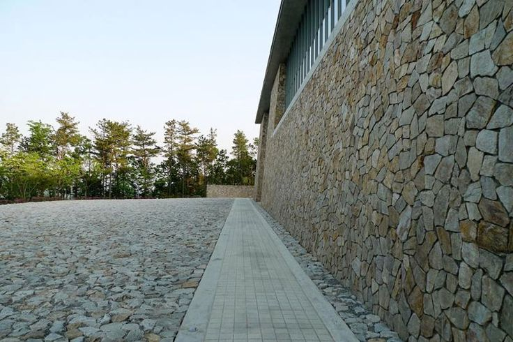 tadao ando's hansol museum in korea sits on top of a mountain - limestone taken from the region is used in the open areas and façade of the architecture