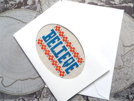 A large cross stitch card, 5 x 7 inches, horizontal, white with an oval window.  A happy encouragement type card.