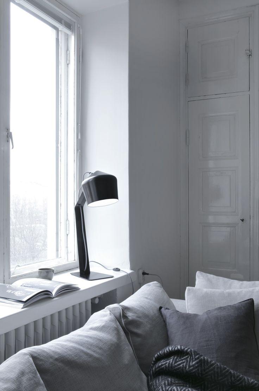 Musta Innolux Pasila -pöytävalaisin ikkunalaudalla. Design by Juho Pasila.