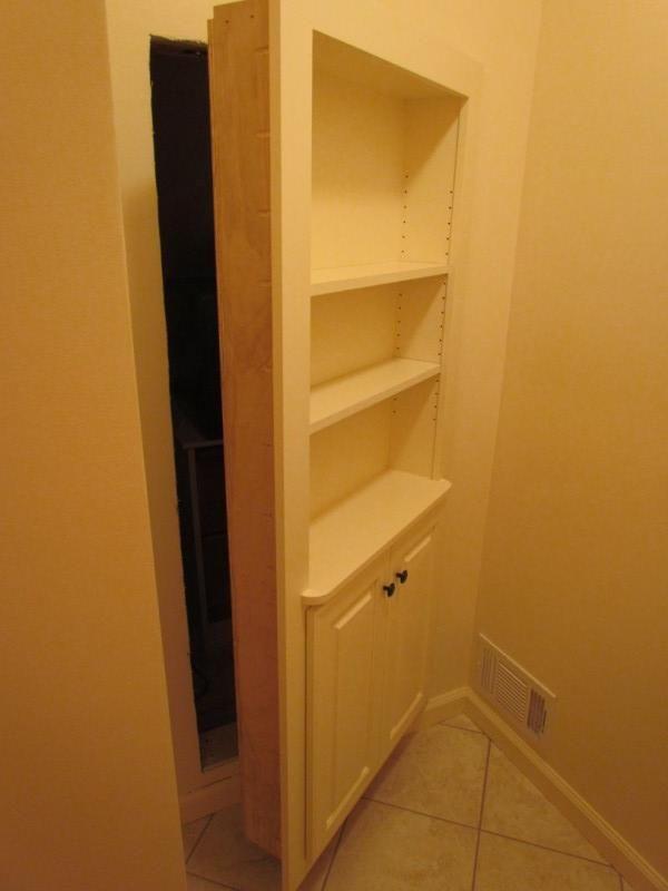 hidden storage area leading to attic storage bookshelf as the door