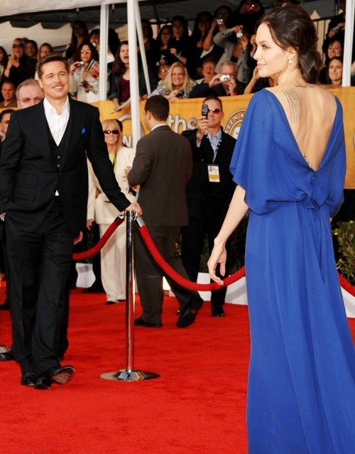 Brad Pitt and Angelina Jolie; how cute, he's just standing back looking at her <3