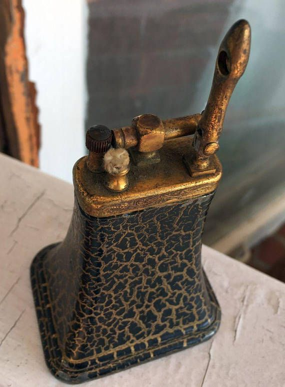 Dies ist eine sehr einzigartige Kuhglocke geformt Tischfeuerzeug aus dem späten 1800 bis Anfang 1900, gemusterten schwarz und gold Farbe im ganzen mit verziert Messing-Elemente an der Spitze. Diese heller verfügt über eine Aufhebung Arm, die den Docht macht, und eine Messing Montage