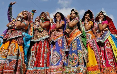 Indian women in traditional costumes perform the Garba dance before the Navratri festival that celebrates the Hindu goddess Durga