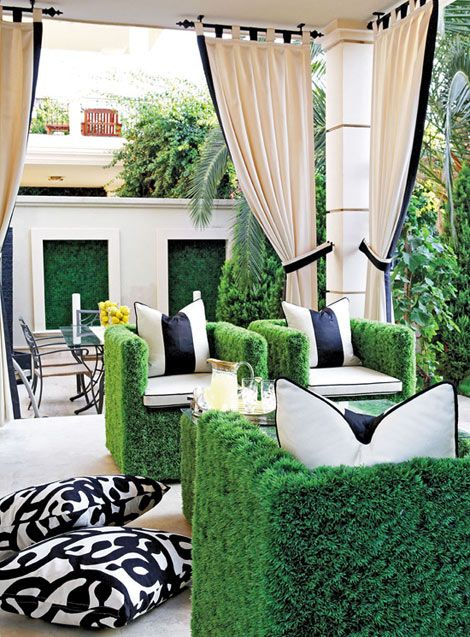 "Terrace    Green patio chairs; chair fabric (""Faux Grass""); seat cushions (""Brava"" #103, cream with ""Magnifico Jet"" contrast welt); striped pillows (""Brava"" #103, cream, and ""Magnifico Jet""); drapery (""Brava"" #103, cream); trim ""Magnifico Jet""); floor pillows: Dorya Interiors, 855/873-6792, www.doryainteriors.com."