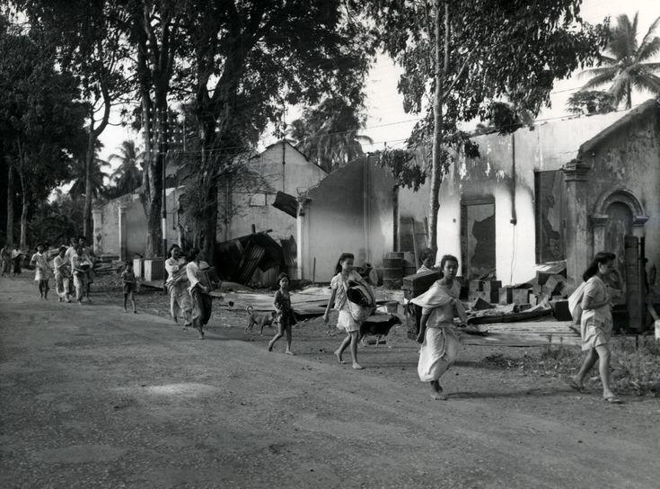 Vluchtelingen met schamele bezittingen keren terug in het verwoeste Tjilatjap tijdens de eerste politionele actie op Midden-Java Indonesië, circa 28 juli 1947.