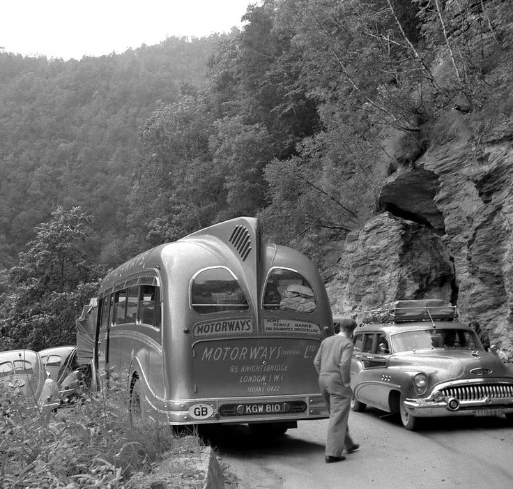 Early 1950's British sightseeing bus, pre-1953 Beetles, and a Buick station wagon navigate a mountain road