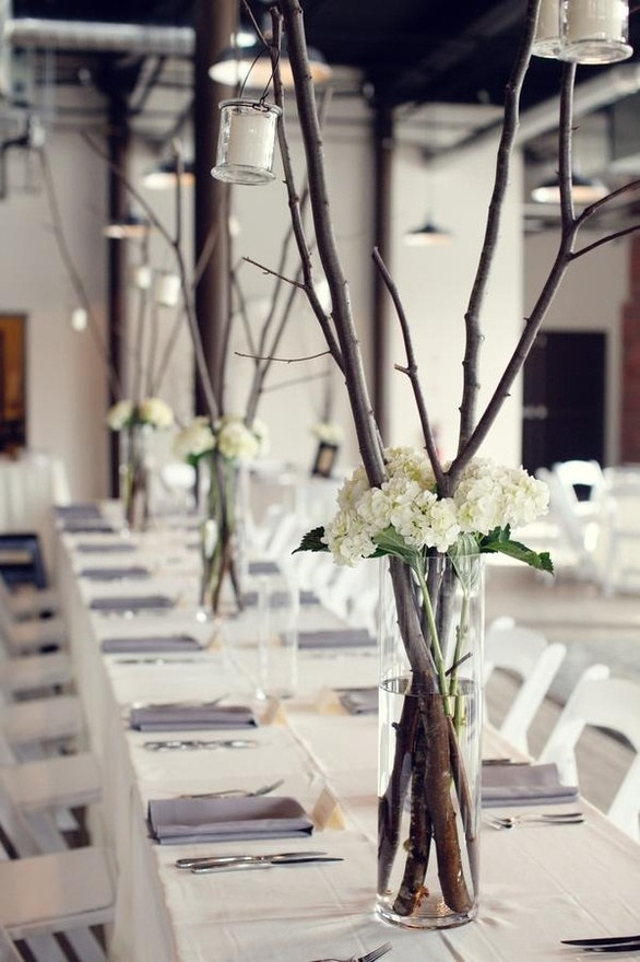 possible branch centerpiece with flowers as the tall decor next to the short flower centerpieces