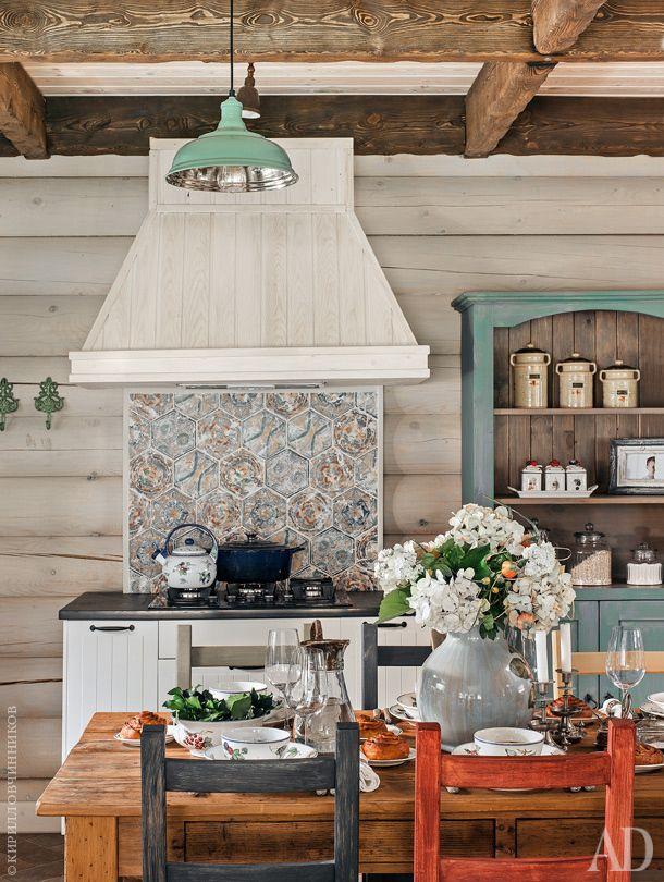 Фрагмент кухни. Фартук над плитой выложен изразцами. Вокруг стола — стулья IКЕА, покрашенные декораторами в разные цвета.