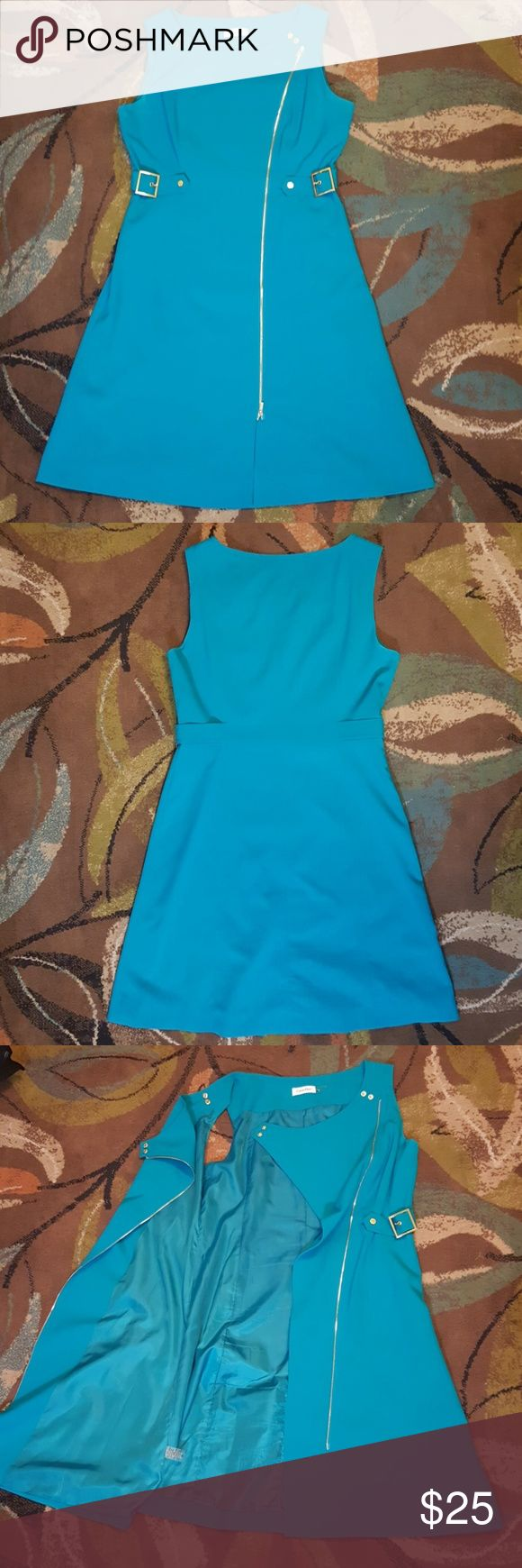 Cerulean Blue Calvin Klein Dress - Size 10 This dress has gold accents that pop against the blue. The buckles cinch the waist to give an hour glass figure. The entire dress unzips and unbuttons in the front if slipping over the head won't do, there are double zippers if you wanted to partly unzip the top or bottom. Its also surprisingly water resistant, water just beads up and runs off.    Dry clean only Calvin Klein Dresses