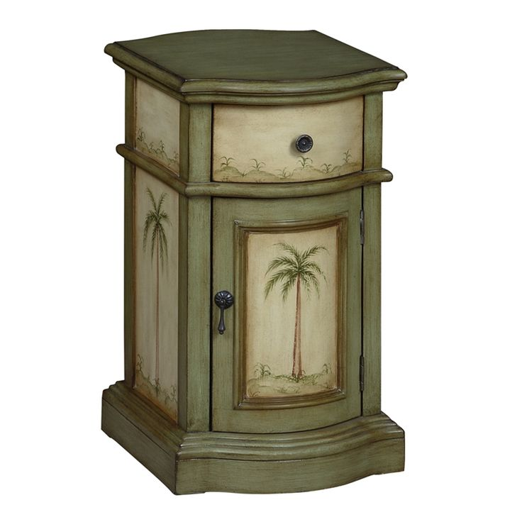 Quietly tropical, this chair side storage cabinet is a beach-inspired accent. The hand painted palm trees and sand dunes adorn all sides, and are enhanced by the Largo Green and cream color palette. The scallop shape and decorative drawer pulls are also important details for this one drawer and one door storage accessory.