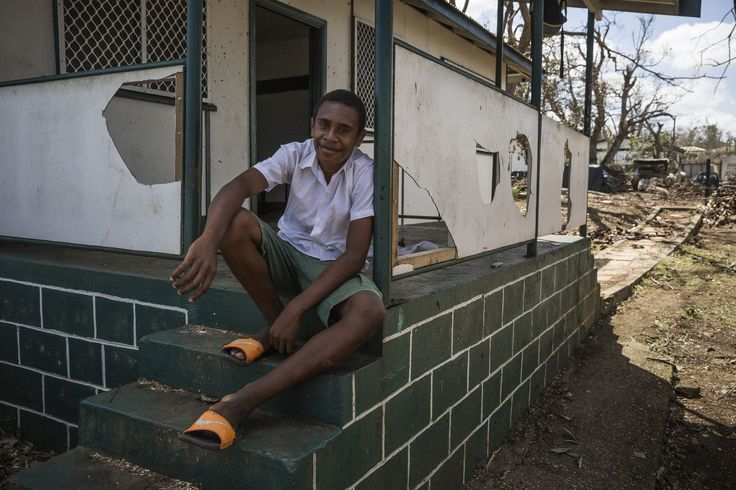 14-year-old William sits in front of his badly damaged classroom in Port Vila, Vanuatu.