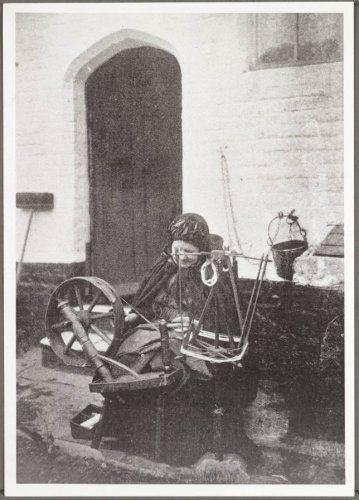 De spinster werd geportretteerd op de binnenkoer van een Brugs godshuis. Ze draagt een Brugse kapmantel.
