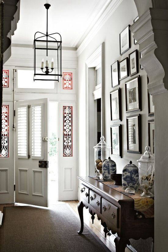 Love the framed art display over console; perfect lantern and Beautiful – somewhat eclectic – glass surrounding door.