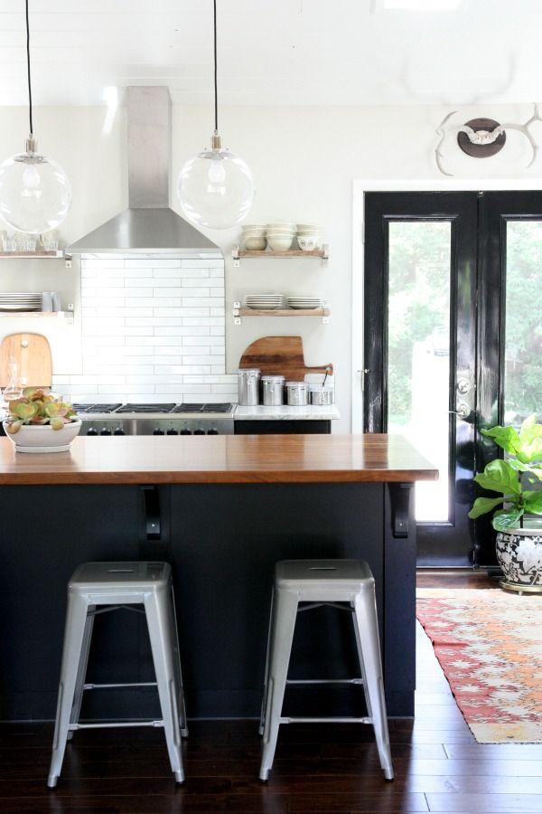Walnut tops the island. Solid surface countertops elsewhere, open shelving, metal stools.