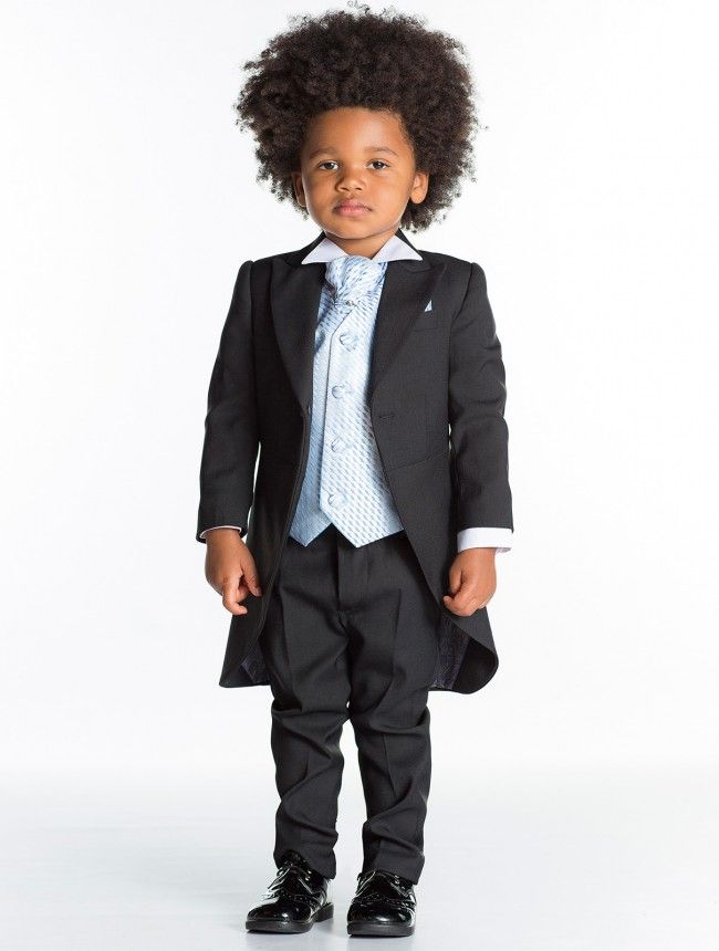 Black long tail suit with a fleck patterned waistcoat, a wing collar white shirt and cravat.