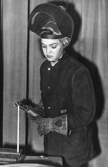 An industrial clinic program during World War II educates women students in general machine shop work. On December 17, 1942, Annie Wells, dressed in clothing suitable for welding work, her face shield ready to be pulled into position, demonstrates the first stage of welding. (The Detroit News/)